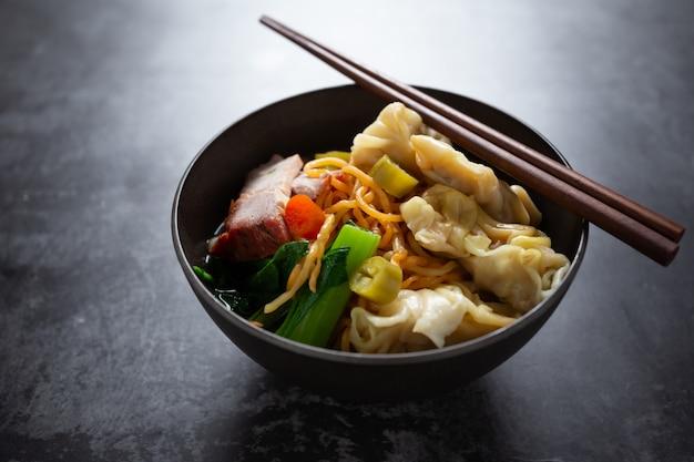Tagliatella all'uovo con carne di maiale arrosto rossa e wonton sul tavolo. Foto Gratuite