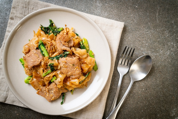 Tagliatella di riso in padella con salsa di soia nera e carne di maiale e cavolo nero Foto Premium