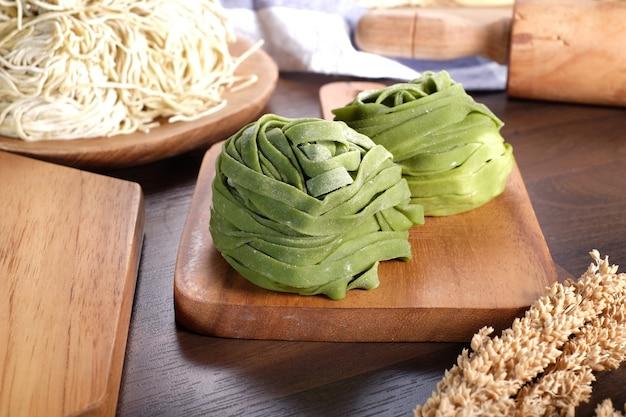 Tagliatelle crude verdi sulla tavola di legno Foto Premium