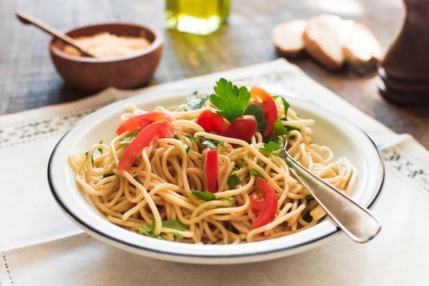 Tagliatelle deliziose cucinate sul piatto bianco sopra il placemat Foto Gratuite