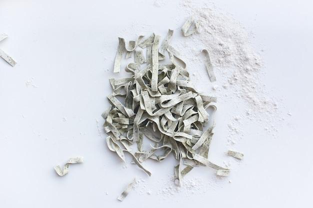 Tagliatelle di pasta coperte di farina con un rullo di legno su uno sfondo bianco Foto Gratuite
