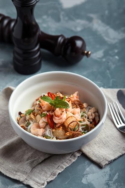 Tagliatelle di riso con gamberetti e frutti di mare, tagliatelle piccanti di stile asiatico in ciotola. Foto Premium