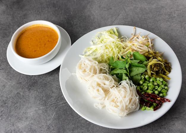 Tagliatelle di riso con salsa al curry di pesce servita con verdure, kanom jeen nam ya cucina tradizionale tailandese Foto Premium