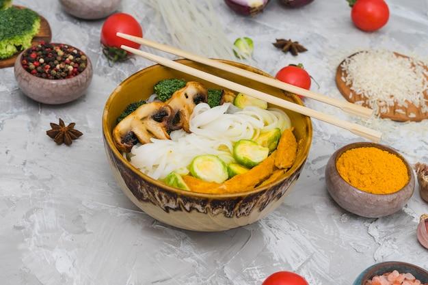 Tagliatelle di riso cotte; fungo; cavoletti di bruxelles e pollo fritto in una ciotola con le bacchette sulla superficie strutturata di cemento Foto Gratuite