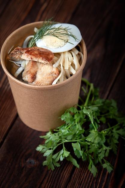 Tagliatelle di tazza di carta con il pollo e le uova su fondo di legno con le erbe Foto Premium