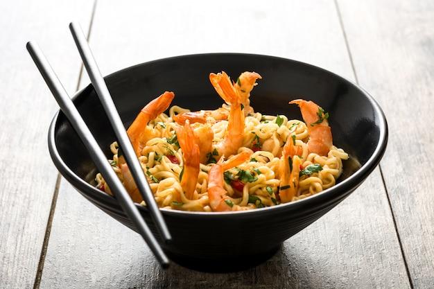Tagliatelle e gamberetti con le verdure in ciotola nera sulla tavola di legno Foto Premium