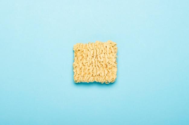 Tagliatelle istantanee cinesi su una superficie blu. il concetto di cibi pronti, fast food, cibo spazzatura. vista piana, vista dall'alto. Foto Premium
