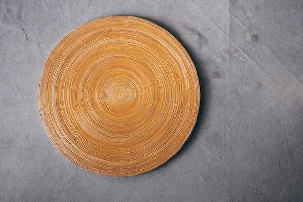 Tagliere di legno in bianco sulla tavola con la tovaglia grigia con il fondo della macchia. Foto Premium