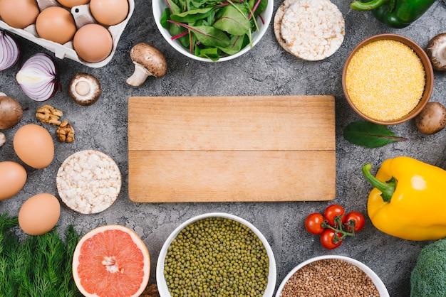 Tagliere in legno circondato con ingredienti su sfondo concreto Foto Gratuite