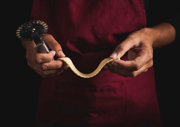 Taglierina e pasta della pizza della tenuta dell'uomo del primo piano Foto Gratuite