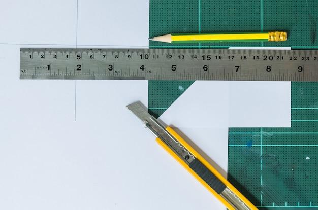 Taglierina, matita di legno e righello sulla vecchia priorità bassa di gomma verde del rilievo Foto Premium