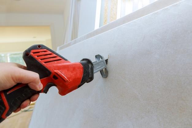 Taglio del cartongesso della mano del muro a secco con la sega sporca di lerciume Foto Premium