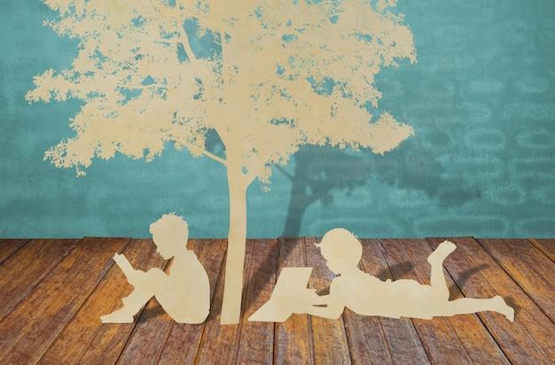 Taglio della carta dei bambini leggere un libro sotto l'albero Foto Gratuite