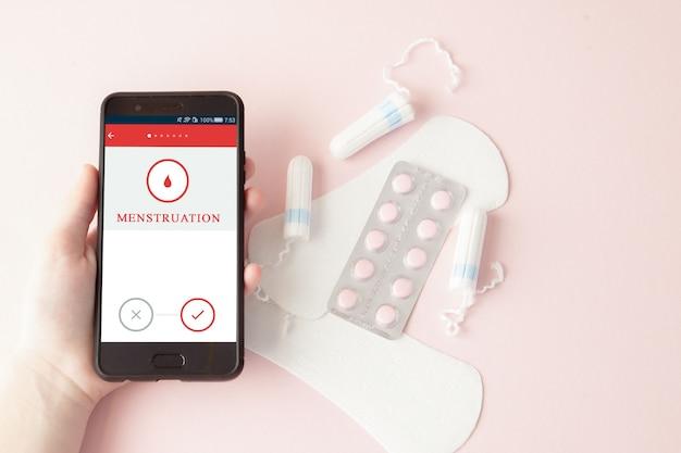 Tampone, assorbenti femminili e sanitari per giorni critici, calendario femminile, pillole antidolorifiche durante le mestruazioni su uno sfondo rosa. tracciamento del ciclo mestruale e dell'ovulazione Foto Premium