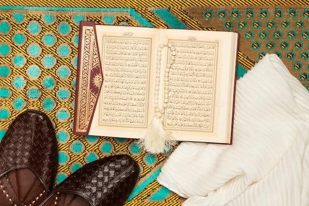 Tappetino con le scarpe, asciugamano e libro sacro Foto Gratuite