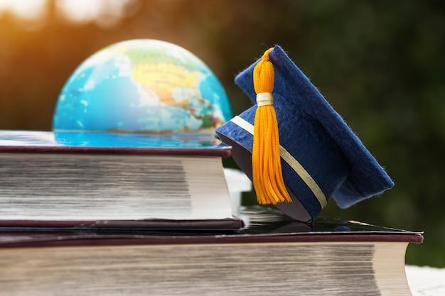 Tappo blu di graduazione sul manuale di apertura con sfocatura del programma di modello del globo del mondo della terra dell'america nella stanza della biblioteca della città universitaria Foto Premium