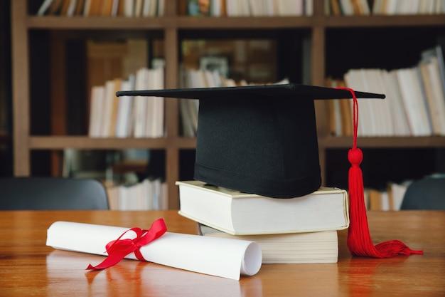 Tappo di laurea nero con laurea sul tavolo di legno nella libreria. laurea Foto Premium