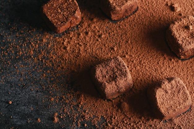 Tartufo cosparso di cacao. caramelle di cioccolato fondente in cacao in polvere su uno sfondo marrone scuro Foto Premium