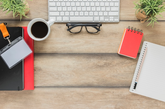 Tastiera con occhiali vicino stazionario e tazza di caffè sul tavolo Foto Gratuite
