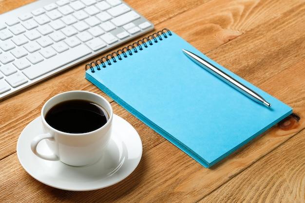 Tastiera del computer, blocco note e notebook per le note, una tazza di caffè o tè, su un tavolo di legno. soggetti di lavoro di un uomo d'affari o manager sul posto di lavoro. Foto Premium