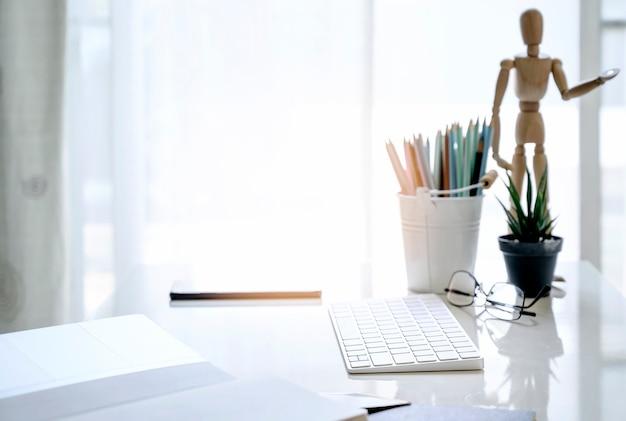 Tastiera di computer bianca del modello con i rifornimenti nella stanza bianca, concetto di lavoro a casa Foto Premium