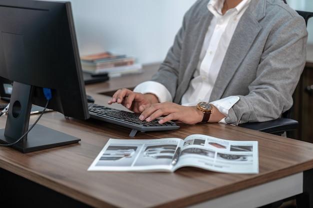 Tastiera di computer digitante della mano asiatica dell'uomo d'affari del primo piano in ufficio Foto Premium