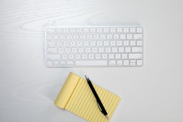 Tastiera senza fili e blocco note giallo sul tavolo Foto Gratuite
