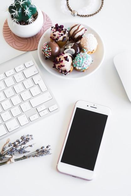 Tastiera vicino smartphone, bracciali, mouse del computer e biscotti sul piatto Foto Gratuite