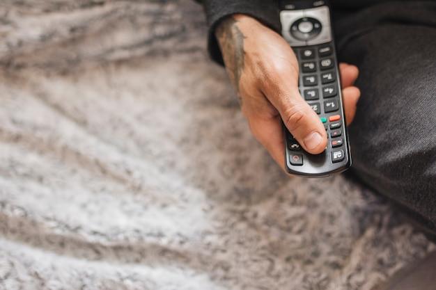 Tatuaggio mano che tiene il telecomando Foto Gratuite