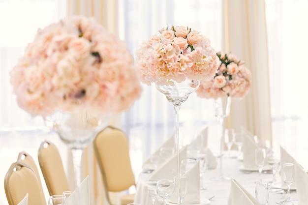 Tavola apparecchiata per la cena di evento con posate e bicchieri, decorata con composizioni floreali in vasi. Foto Premium
