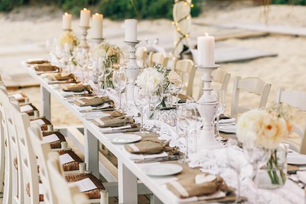 Tavola da pranzo lunga decorata con panno di lino e candele bianche Foto Gratuite
