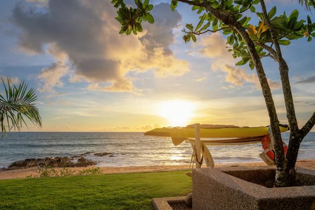 Tavola da windsurf e bagnino di colorato tramonto sul mare. sabbia e palme Foto Premium