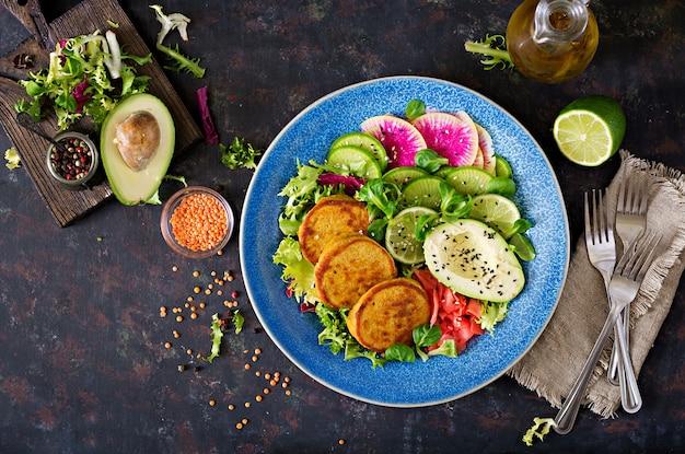 Tavola dell'alimento della cena della ciotola di buddha del vegano. cibo salutare. ciotola da pranzo vegana sana. frittella con lenticchie e ravanelli, insalata di avocado. disteso. vista dall'alto Foto Premium
