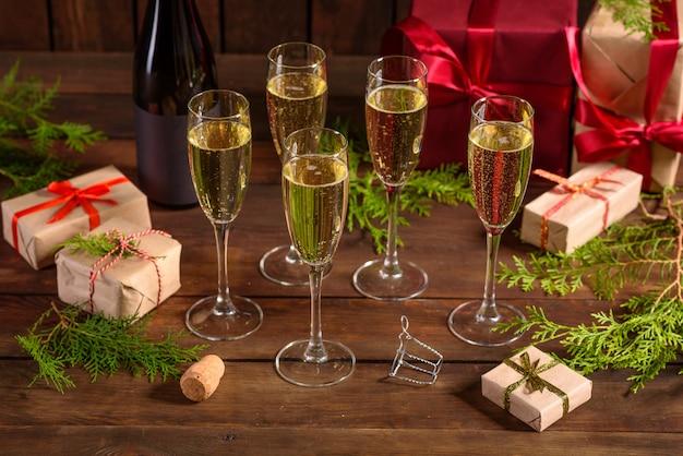 Tavola delle vacanze di natale con bicchieri e una bottiglia di vino di champagne Foto Premium
