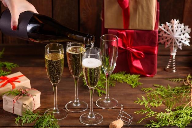 Tavola delle vacanze di natale con bicchieri e una bottiglia di vino Foto Premium