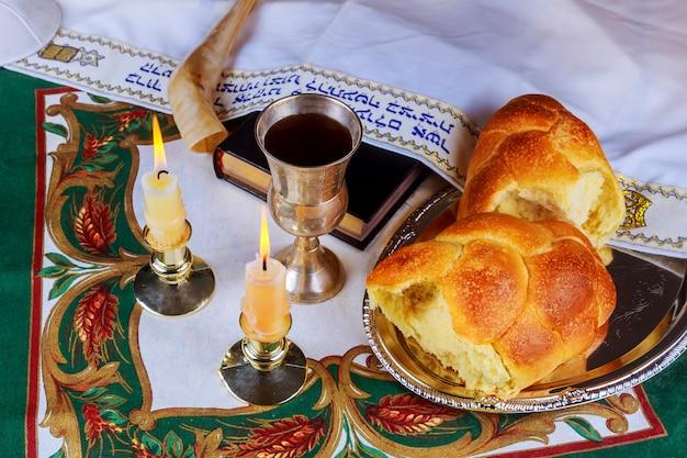 Tavola dello shabbat con pane challah, candele e kippah. Foto Premium