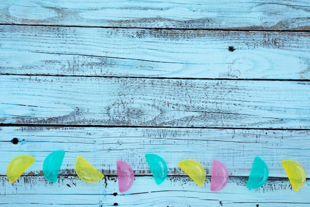 Tavola di legno blu distesa con limoni di plastica colorati Foto Gratuite
