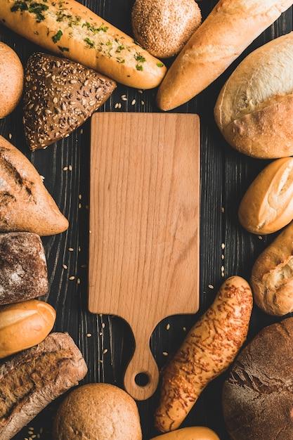 Tavola di legno circondata da pagnotte di pane Foto Gratuite