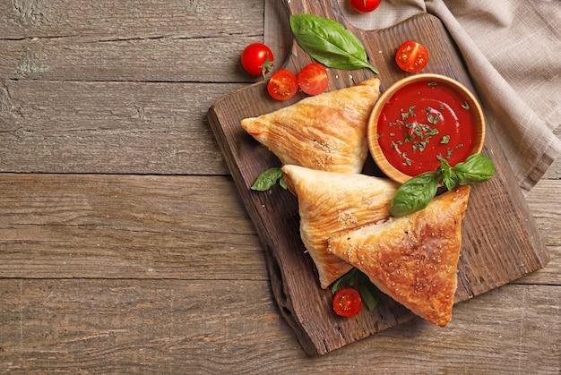 Tavola di legno con deliziose samosa di carne sul tavolo Foto Premium