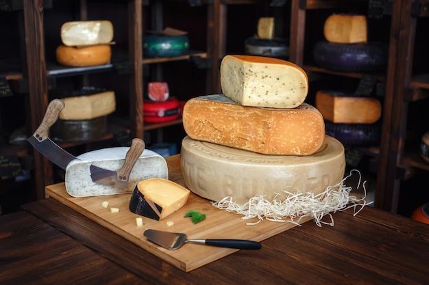 Tavola di legno con diversi tipi di delizioso formaggio sul tavolo Foto Premium