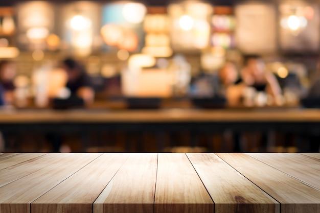 Tavola di legno con sfocatura sfondo della caffetteria. Foto Premium