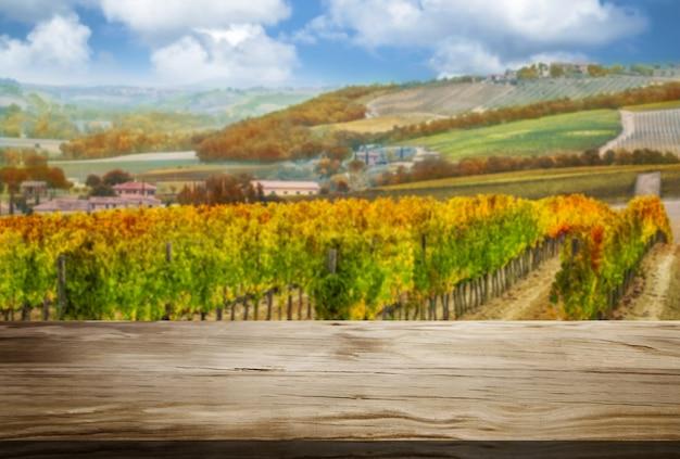 Tavola di legno nel paesaggio del paese della vigna di autunno. Foto Premium