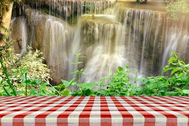 Tavola di legno vuota con bella scenografia della cascata e foglie verdi. Foto Premium