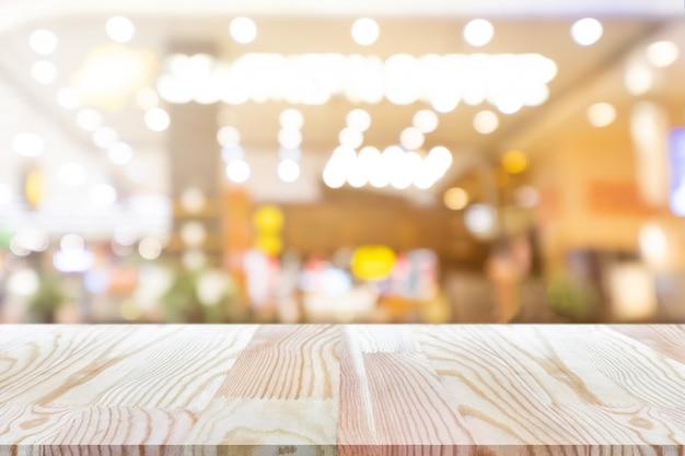 Tavola di legno vuota di prospettiva sulla cima sopra il fondo della caffetteria della sfuocatura Foto Premium