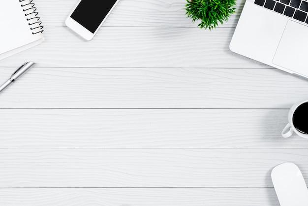 Tavola ed attrezzatura di legno bianche della scrivania per lavorare con caffè nero nella vista superiore e nel concetto piano del raggio. Foto Premium