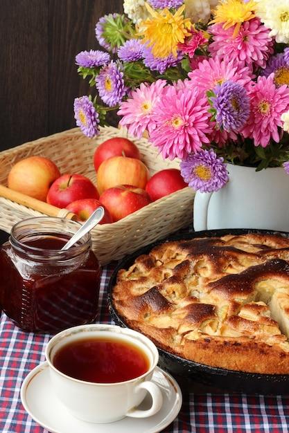 Tavola morta con torta, mele rosse, marmellata, tè in tazza e un mazzo di crisantemi rosa Foto Premium