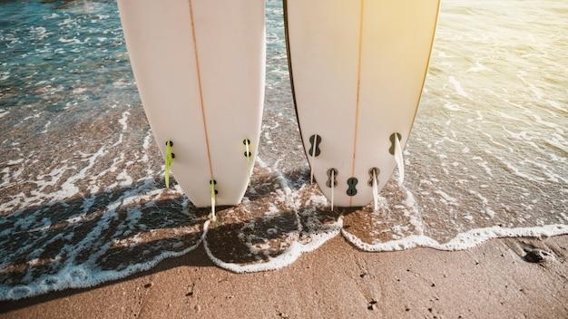 Tavole da surf bianco sulla costa vicino all'acqua Foto Gratuite