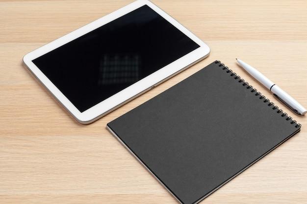 Tavoletta digitale con blocco note, forniture e tazza di caffè sul desktop. Foto Premium