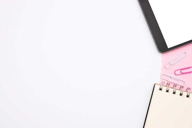 Tavoletta digitale e diario a spirale con graffetta su sfondo bianco Foto Gratuite