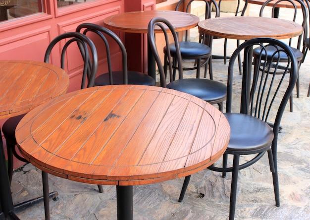 Tavoli in legno e sedie nere allestiti per pranzare fuori dal bar Foto Premium